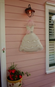 They hung this miniature bridal gown on the front porch.
